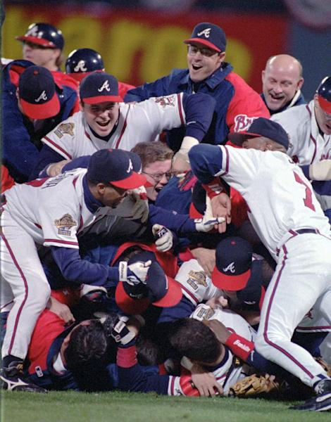 FILE - In this Oct. 28, 1995, file photo, the Atlanta Braves celebrate their 1995 World Series win against the Cleveland Indiants at Atlanta Fulton County Stadium in Atlanta. After a one-year delay caused by the 7 and a half-month players' strike, the expanded playoffs began in 1995, when teams played a 144-game schedule because of the walkout. The top teams met that October, with Atlanta defeating Cleveland in six games. (AP Photo/Andrew Innerarity, File)