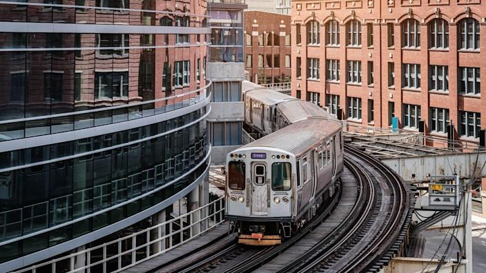Chicago typical silver colored commuter train moving on elevated tracks to railroad station in between urban city buildings of Chicago, Illinois, USA.