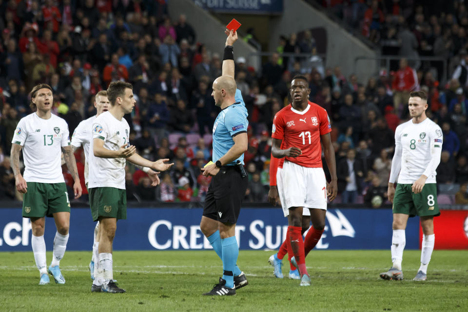 Referee Szymon Marciniak shows the red card to Ireland defender Seamus Coleman, 2nd left, during their Euro 2020 qualifying Group D soccer match at the Stade de Geneve, in Geneva, Switzerland, Tuesday, Oct. 15, 2019. (Salvatore Di Nolfi/Keystone via AP)