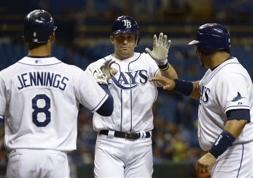 Tampa Bay Rays' Evan Longoria, center, is met at home plate by Desmond Jennings, left, and Jose Molina after Longoria knocked them in on a three-run home run during the second inning of a baseball game against the Toronto Blue Jays in St. Petersburg, Fla., Saturday, Sept. 22, 2012.(AP Photo/Phelan M. Ebenhack)