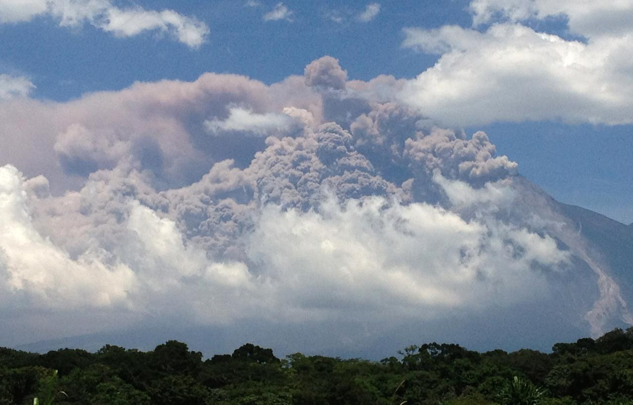 """In this image with a cell phone, plumes of smoke rise from the Volcan de Fuego or Volcano of Fire as seen from Palin, south of Guatemala City, Thursday, Sept. 13, 2012. The volcano is spewing lava and ash and the director of the national disaster agency says officials are carrying out """"a massive evacuation of thousands of people"""" in five communities. (AP Photo/Moises Castillo)"""