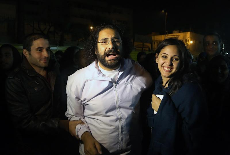 Alaa Abdel-Fattah, center in white, a prominent activist and a leading figure in the 2011 uprising against Egyptian autocrat Hosni Mubarak, is welcomed by his wife after he was released from the main central security office in Cairo, Egypt, Sunday, March 23, 2014. Abdel-Fattah was arrested from his home on Nov. 28, 2013, and he and his wife accuse police of attacking them during the arrest. Egyptian court on Sunday ordered the release on bail pending trial of Abdel-Fattah charged with breaking a new law that heavily restricts protests, after he spent nearly four months in jail. (AP Photo/Roger Anis, El Shorouk Newspaper) EGYPT OUT