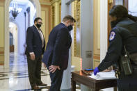 New member Rep. Guy Reschenthaler, R-Pa., passes through a metal detector before entering the House chamber, a new security measure put into place after a mob loyal to President Donald Trump stormed the Capitol, in Washington, Tuesday, Jan. 12, 2021. The House is trying to push the vice president and Cabinet to act even more quickly to remove President Donald Trump from office, with Democrats set to pass a resolution calling on Vice President Mike Pence to invoke constitutional authority under the 25th Amendment to oust Trump. (AP Photo/J. Scott Applewhite)