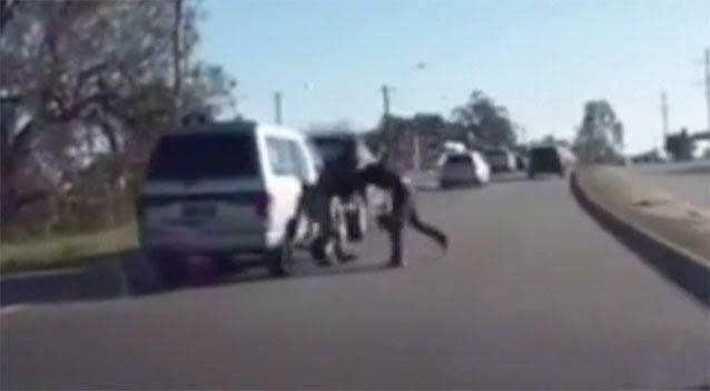 Traffic was held up as two men fought. Source: 7 News