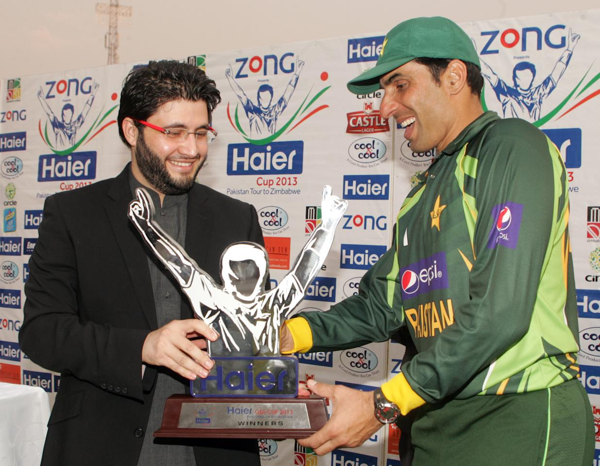 Pakistan's captain Misbah Ul Haq (R) receives the series trophy after winning the final game of the three ODI cricket series matches between Pakistan and Zimbabwe at the Harare Sports Club August 31, 2013.      AFP PHOTO / JEKESAI NJIKIZANA        (Photo credit should read JEKESAI NJIKIZANA/AFP/Getty Images)