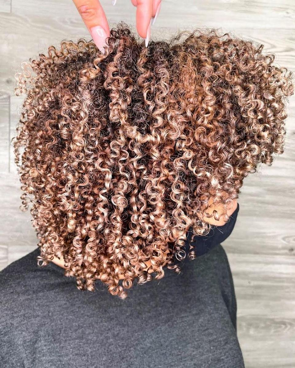 """If you have tighter curls, it can be scary to go lighter, but <a href=""""https://www.instagram.com/jamilapowell/"""" rel=""""nofollow noopener"""" target=""""_blank"""" data-ylk=""""slk:Jamila Powell"""" class=""""link rapid-noclick-resp"""">Jamila Powell</a>, owner of Miami's curl-centric Maggie Rose salon says not to worry. """"These highlights take your hair up a notch, and since they don't require foils, cause minimal damage,"""" she says. """"This style works best for those with curls who want a sun-kissed look for the summer months. Ask your stylist to hand-paint the curls throughout your hair in order to achieve this look."""""""