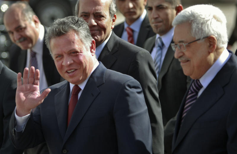 King Abdullah II of Jordan, left, gestures during a welcoming ceremony with Palestinian President Mahmoud Abbas, prior to their meeting in the West Bank city of Ramallah, Thursday, Dec. 6, 2012. Jordan's King Abdullah II has begun a brief visit to the West Bank in support of Palestinian President Mahmoud Abbas' successful bid for U.N. recognition of a state of Palestine. (AP Photo/Majdi Mohammed)
