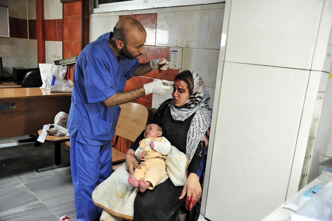 ATTENTION EDITORS - VISUALS COVERAGE OF SCENES OF DEATH AND INJURYA wounded woman carries a baby as she receives treatment inside a hospital after multiple bomb blasts hit a southern district of Damascus, Syria, in this handout picture provided by SANA on February 21, 2016. REUTERS/SANA/Handout via Reuters ATTENTION EDITORS - THIS PICTURE WAS PROVIDED BY A THIRD PARTY. REUTERS IS UNABLE TO INDEPENDENTLY VERIFY THE AUTHENTICITY, CONTENT, LOCATION OR DATE OF THIS IMAGE. FOR EDITORIAL USE ONLY. NOT FOR SALE FOR MARKETING OR ADVERTISING CAMPAIGNS. THIS PICTURE IS DISTRIBUTED EXACTLY AS RECEIVED BY REUTERS, AS A SERVICE TO CLIENTS.      TPX IMAGES OF THE DAY