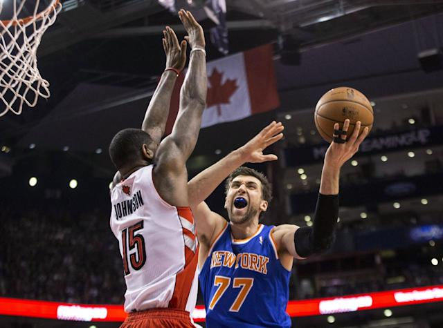 New York Knicks' Andrea Bargnani, right, shoots on Toronto Raptors' Amir Johnson during the first half of an NBA basketball game in Toronto on Saturday, Dec. 28, 2013. (AP Photo/The Canadian Press, Chris Young)