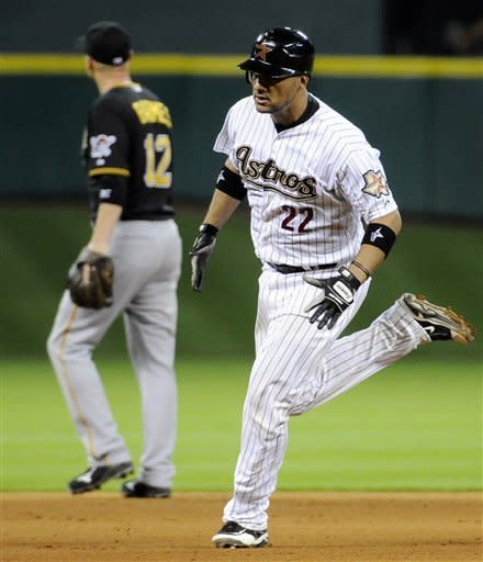 Houston Astros' Carlos Corporan (22) rounds the bases in front of Pittsburgh Pirates' Clint Barmes (12) on a solo home run in the eighth inning of a baseball game, Thursday, July 26, 2012, in Houston. (AP Photo/Pat Sullivan)