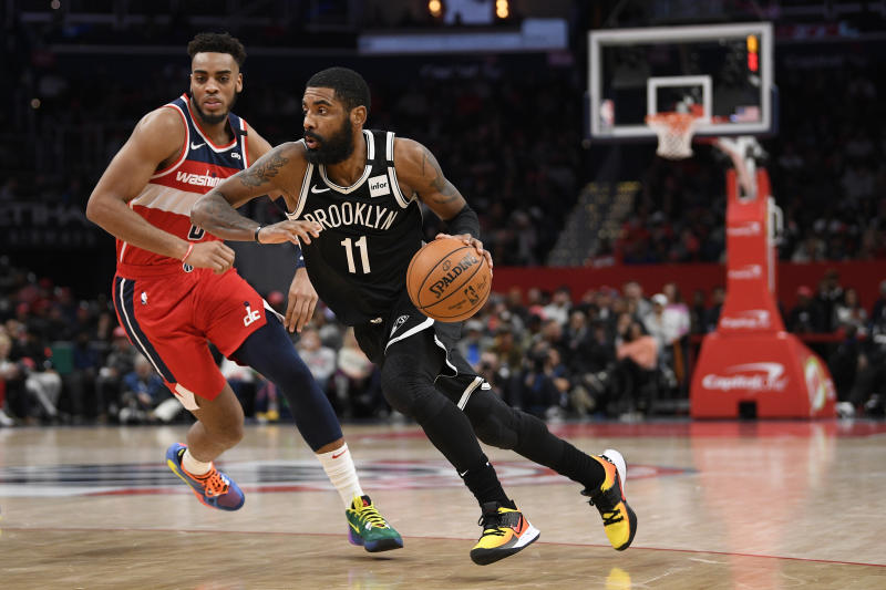 Brooklyn Nets guard Kyrie Irving (11) dribbles the ball against Washington Wizards forward Troy Brown Jr. (6) during the second half of an NBA basketball game, Saturday, Feb. 1, 2020, in Washington. The Wizards won 113-107. (AP Photo/Nick Wass)