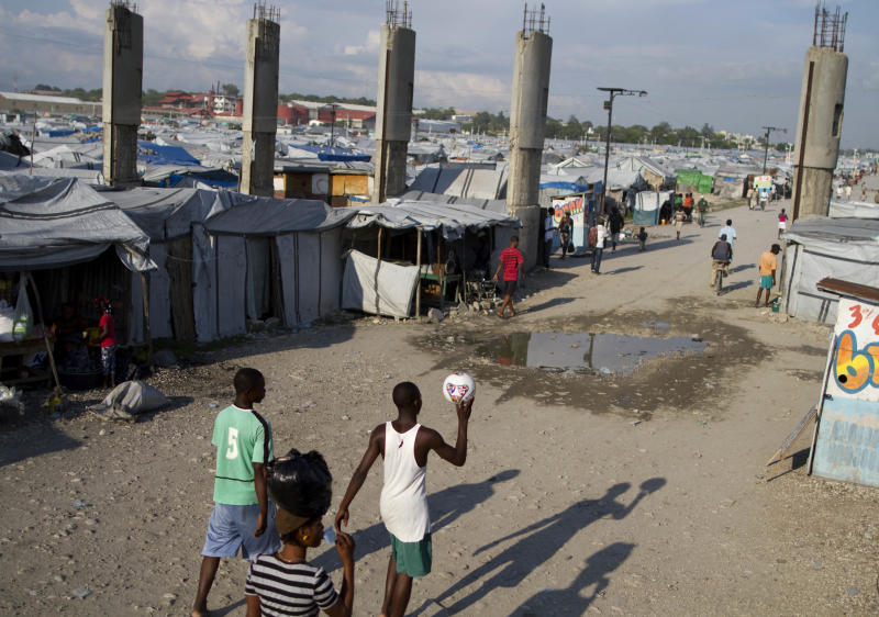 In this Thursday, May 10, 2012 photo, people walk inside the Jean Marie Vincent camp for people displaced by the devastating 2010 earthquake in Port-au-Prince, Haiti. Despite the nearly 12-month standoff between the Haitian parliament and President Michel Martelly, his first year has yielded modest gains despite big obstacles. Asked to name his accomplishments, Martelly pointed out the school-tuition program, the clearing of major camps, the repair of damaged homes and, most controversially, outright evictions from the flimsy shelters of the overcrowded temporary settlements. (AP Photo/Dieu Nalio Chery)