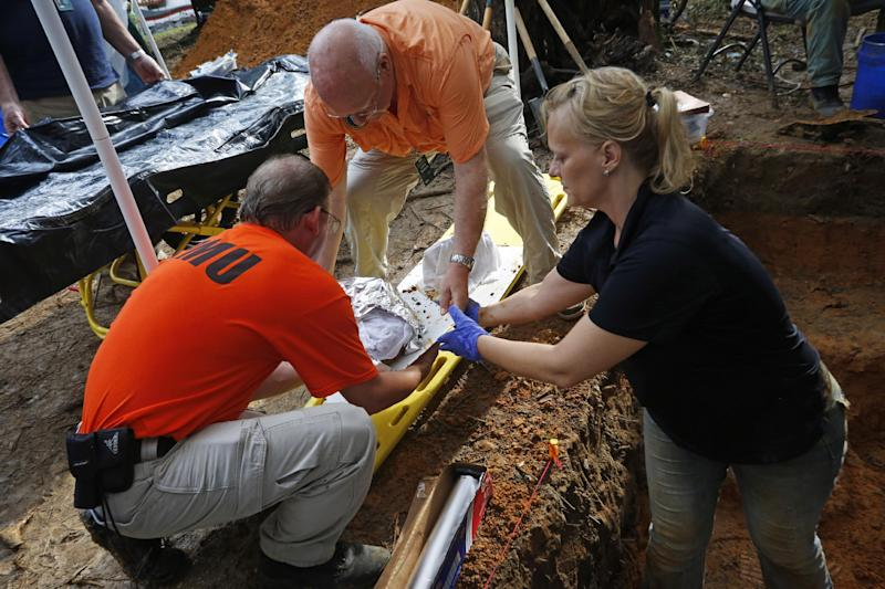 CORRECTS NAME TO LARRY BEDORE- Jason Byrd, left, and Larry Bedore,center, both with the Florida Emergency Mortuary Operations Response System, help University of South Florida assistant professor Dr. Erin Kimmerle, right, load remains exhumed from a grave at the Arthur G. Dozier School for Boys on September 2, 2013 in Marianna. Anthropologists from the University of South Florida removed the first remains from the cemetery at the Arthur G. Dozier School for Boys in Marianna, Fla on Sept. 2, 2013.