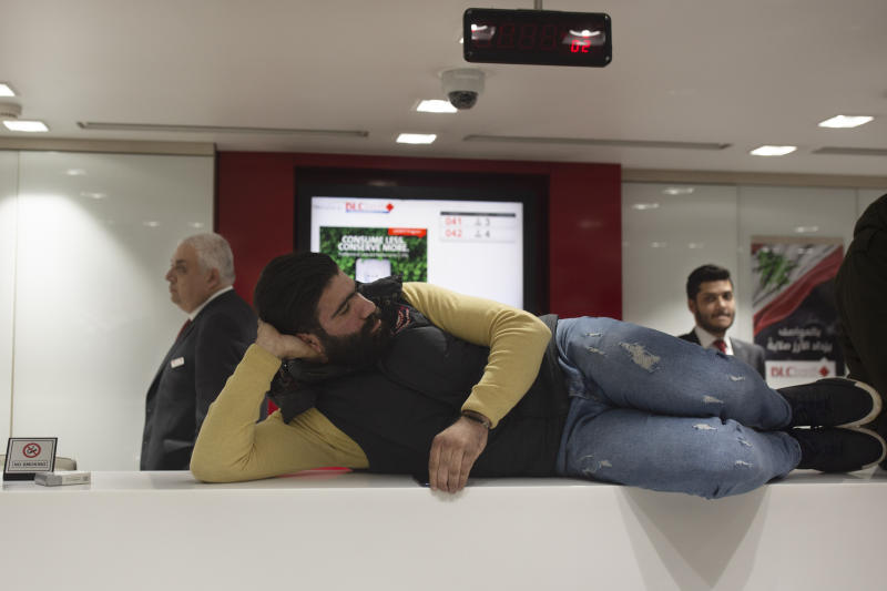 A Lebanese protester reclines on a bank counter during a sit-in at the Hamra branch of BLC Bank Dec. 28, 2019 in Beirut, Lebanon. Dozens of Lebanese protesters held a brief sit-in inside a bank in Beirut and another in the country's south on Saturday, part of their focus on banking policies they complain are inefficient and corrupt.(AP Photo/Maya Alleruzzo)