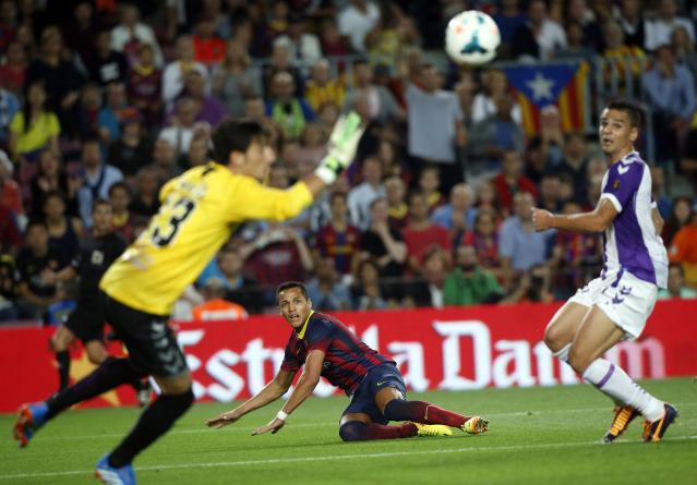 Barcelona's Alexis Sanchez (C) looks to the ball as Real Valladolid's goalkeeper Diego Marino (L) tries to block it during their Spanish first division soccer match at Camp Nou stadium in Barcelona October 5, 2013. REUTERS/Albert Gea (SPAIN - Tags: SPORT SOCCER)
