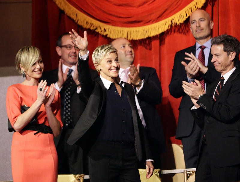 Entertainer Ellen DeGeneres, second from front left, waves as she is introduced, with wife Portia de Rossi, left, before DeGeneres receives the 15th annual Mark Twain Prize for American Humor at the Kennedy Center, Monday, Oct. 22, 2012, in Washington. (AP Photo/Alex Brandon)