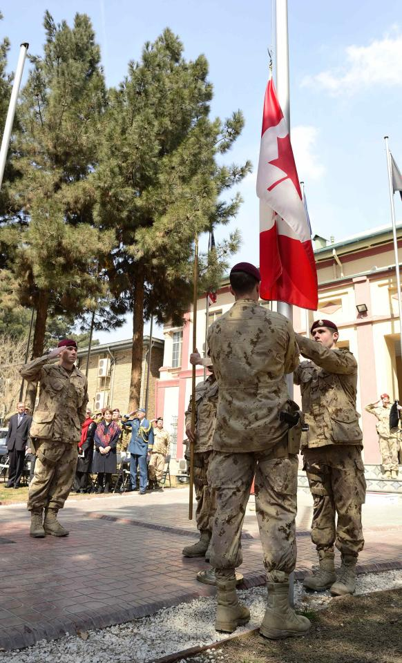 Master Corporal Jordan Taylor (L) salutes as the Canadian flag is lowered at the International Security Assistance Force (ISAF) headquarters during a ceremony marking the end of Canada's 12-year military involvement in Afghanistan, in Kabul March 12, 2014. REUTERS/MCpl Patrick Blanchard/Canadian Forces Combat Camera/Handout via Reuters (AFGHANISTAN - Tags: MILITARY) ATTENTION EDITORS � THIS IMAGE WAS PROVIDED BY A THIRD PARTY. FOR EDITORIAL USE ONLY. NOT FOR SALE FOR MARKETING OR ADVERTISING CAMPAIGNS. THIS PICTURE IS DISTRIBUTED EXACTLY AS RECEIVED BY REUTERS, AS A SERVICE TO CLIENTS