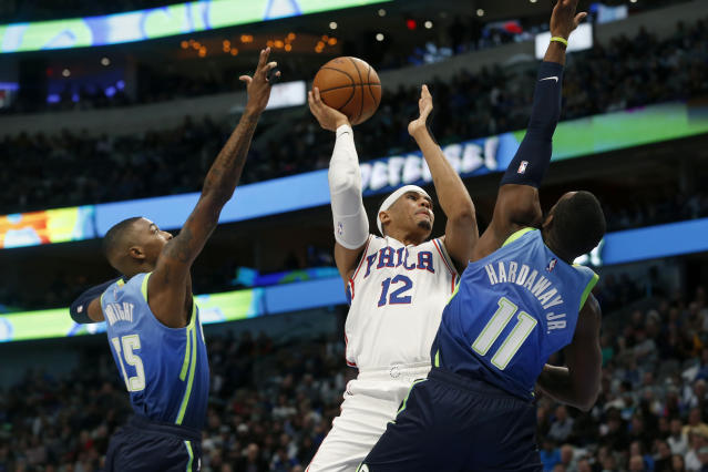 Philadelphia 76ers forward Tobias Harris (12) shoots as he is defended by Dallas Mavericks guards Delon Wright (55) and Tim Hardaway Jr. (11) during the first half of an NBA basketball game in Dallas, Saturday, Jan 11, 2020. (AP Photo/Michael Ainsworth)