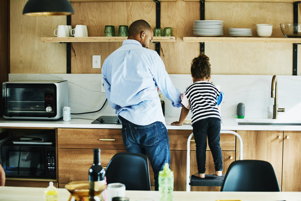 Young girl standing on stool in kitchen while helping father make dinner