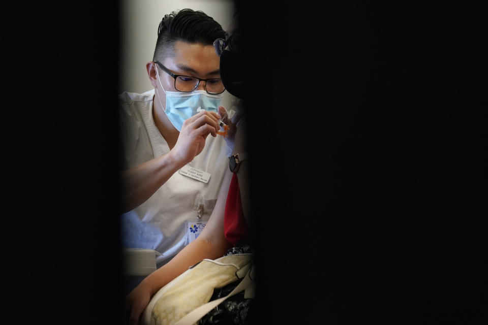 FILE - In this April 26, 2021, file photo, Johnson Shao, a nursing student at the College of Southern Nevada, administers the Moderna COVID-19 vaccine at a vaccination center at UNLV in Las Vegas. Even as restrictions relax across much of the United States, colleges and universities have taken new steps to police campus life as the virus spreads through students who are among the last adults to get access to vaccines. (AP Photo/John Locher)