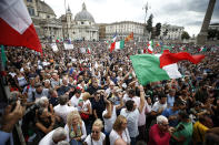 People gather in Piazza del Popolo square during a protest, in Rome, Saturday, Oct. 9, 2021. Thousands of demonstrators protested Saturday in Rome against the COVID-19 health pass that Italian workers, both the public and private sectors, must display to access their workplaces from Oct. 15 under a government decree. (Cecilia Fabiano/LaPresse via AP)