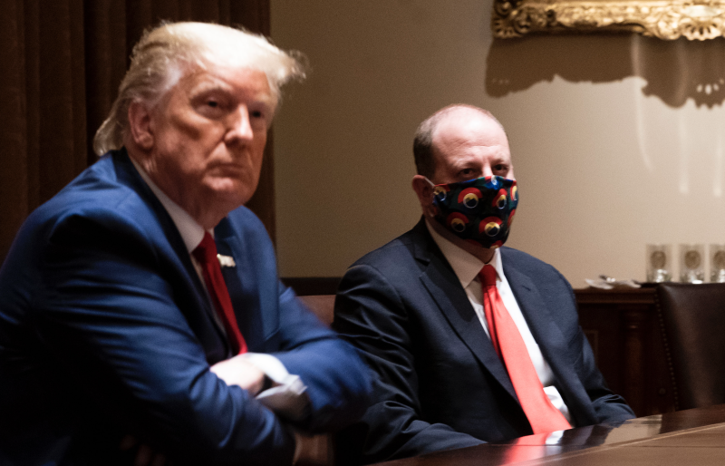 Colorado Governor Jared Polis (C) wears a face mask as U.S. President Donald Trump makes remarks during a meeting in the Cabinet Room of the White House, May 13, 2020 in Washington, DC. (Photo: Doug Mills-Pool/Getty Images)