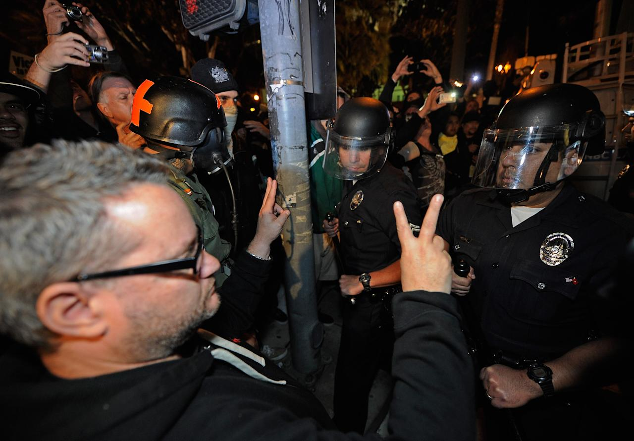 LOS ANGELES, CA - NOVEMBER 28:  Los Angeles Police Officers in riot gear push Occupy LA demonstrators back on the sidewalk in an attempt to clear the streets around Los Angeles City Hall after the deadline to dismantle the occupy campsite expired on November 28, 2011 in Los Angeles, California. Los Angeles Mayor Antonio Villaraigosa last week gave the protesters outside City Hall until 12:01 am today to dismantle their protest campsite and leave.  (Photo by Kevork Djansezian/Getty Images)