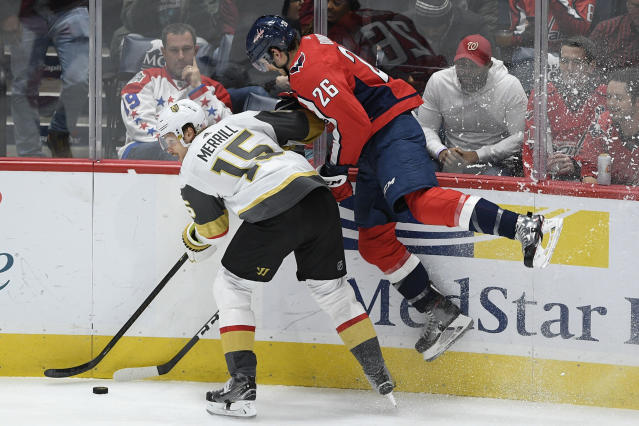 Washington Capitals center Nic Dowd (26) and Vegas Golden Knights defenseman Jon Merrill (15) compete for the puck during the third period of an NHL hockey game Saturday, Nov. 9, 2019, in Washington. The Capitals won 5-2. (AP Photo/Nick Wass)