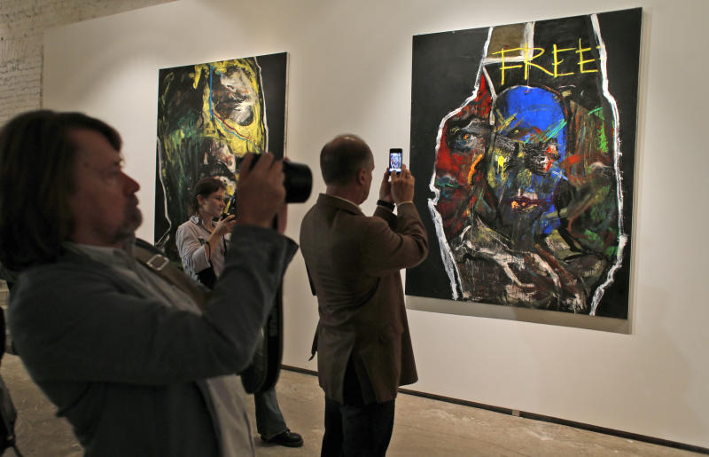 Visitors take photos of paintings by Yevgenia Maltseva at the opening of her exhibition in the Vinzavod art gallery in Moscow, Russia, Thursday, Sept. 20, 2012. A protest by about 15 Russian Orthodox Christian activists has disrupted the opening of a Moscow art exhibit inspired by the jailed members of the punk band Pussy Riot. Riot police dispersed the protesters, detaining nine of them, but then blocked off the area, making it difficult for those who wanted to attend Thursday's opening to get inside. The paintings by Yevgenia Maltseva were inspired by religious icons and the three Pussy Riot members who were jailed for a raucous performance inside a Moscow cathedral to protest Vladimir Putin's rule and his close relationship with the church hierarchy. (AP Photo/Alexander Zemlianichenko)