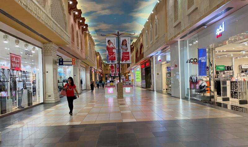 FILE PHOTO: A woman walks in an almost empty mall amid the outbreak of coronavirus disease (COVID-19), in Dubai