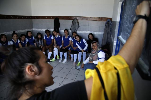 In this Thursday, May 2, 2019 photo, coach of Hestia FC Women's Refugee Soccer team Mary Gavala gives instructions to her players before a friendly game in Athens. Many of the players at Hestia FC weren't allowed to play or even watch soccer matches in their home countries. Hestia FC was set up by the Olympic Truce Centre, a non-government organization created in 2000 by the International Olympic Committee and Greek Foreign Ministry. (AP Photo/Thanassis Stavrakis)