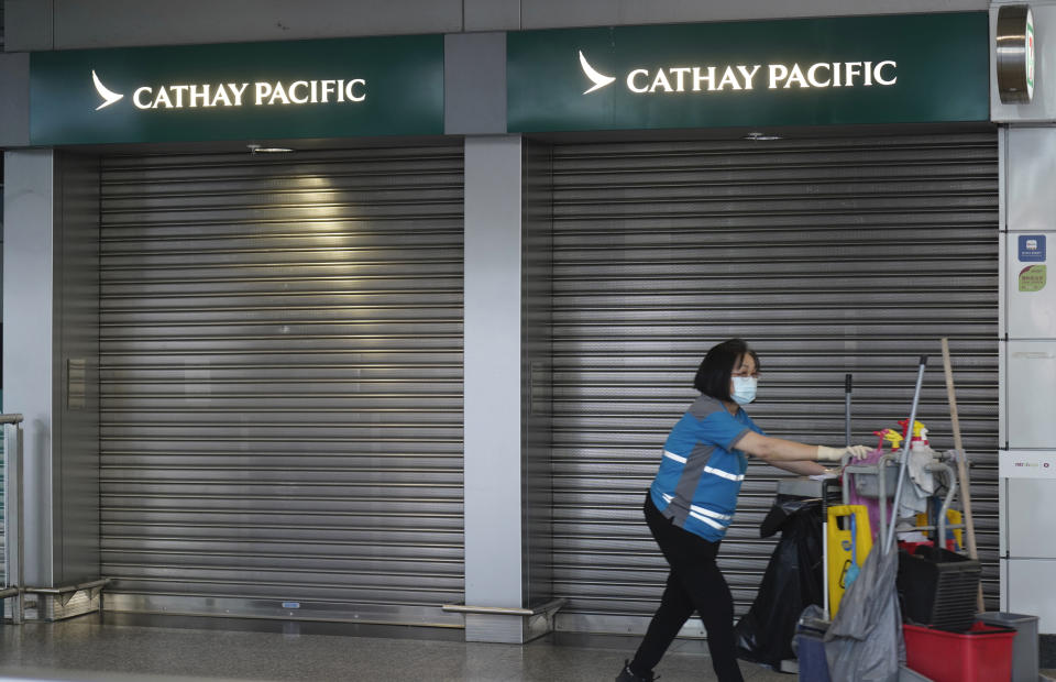 A cleaner walks past a Cathay Pacific booth at the airport train station in Hong Kong Wednesday, Oct. 21, 2020. Hong Kong airline Cathay Pacific Airways on Wednesday said it would cut 8,500 jobs and shut down its regional airline unit in a corporate restructuring, as it grapples with the plunge in air travel due to the pandemic. (AP Photo/Vincent Yu)