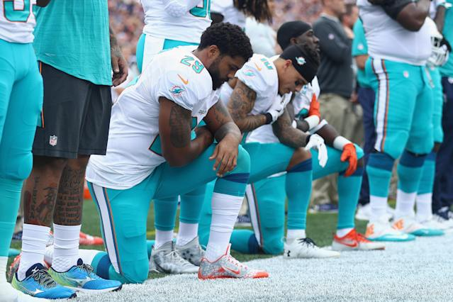Arian Foster (No. 29), Kenny Stills (No. 10), and Michael Thomas (No. 31) of the Miami Dolphins kneel during the national anthem before the game against the New England Patriots at Gillette Stadium on Sept. 18, 2016. (Photo by Maddie Meyer/Getty Images)