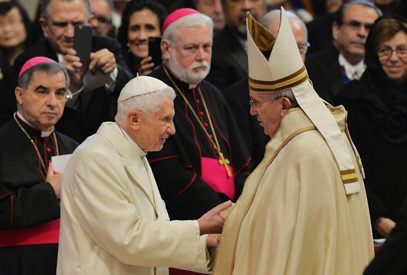 Pope Francis (R) greets Pope Emeritus Benedict XVI at the end of a consistory for the creation of new cardinals on February 14, 2015 at St. Peter's basilica in the Vatican (AFP Photo/Andreas Solaro)