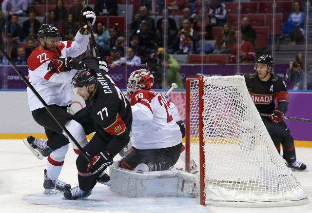 Canada's Jeff Carter is upended by Austria's Thomas Pock in front of Austria's goalie Bernhard Starkbaum during the first period of their men's preliminary round ice hockey game at the 2014 Sochi Winter Olympics, February 14, 2014. REUTERS/Gary Hershorn (RUSSIA - Tags: TPX IMAGES OF THE DAY SPORT ICE HOCKEY OLYMPICS)