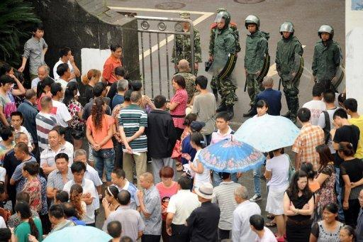 Chinese paramilitary police (top) guard the government offices Shifang in China's Sichuan province on July 4, a day after authorities bowed to violent protests and cancelled plans to build a controversial metals factory. The protests in Shifang city highlighted and fuelled concerns around China over the impacts of rampant economic development on the environment