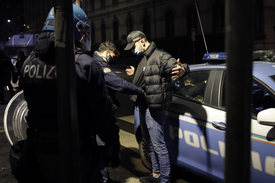 Police detain a man following a protest against the government restriction measures to curb the spread of COVID-19, in Milan Italy, Monday, Oct. 26, 2020. Protesters turned out by the hundreds in Italian several cities and towns on Monday to vent anger, sometimes violently, over the latest anti-COVID-19 rules, which force restaurants and cafes to close early, shutter cinema, gyms and other leisure venues. In the northern city of Turin, demonstrators broke off from a peaceful protest and hurled smoke bombs and bottles at police in the city square where the Piedmont regional government is headquartered. (AP Photo/Luca Bruno)