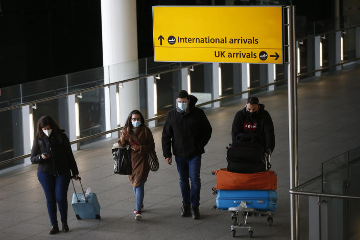 """LONDON, ENGLAND - JANUARY 17: Travelers arrive at Heathrow Airport on January 17, 2021 in London, England. Tomorrow morning the UK will close its so-called """"travel corridors"""" with countries from which arriving travelers were exempt from quarantine requirements. People flying into the UK will now be required to quarantine for 10 days unless they test negative for covid-19 after five days, or unless they qualify for a business-travel exemption. (Photo by Hollie Adams/Getty Images)"""