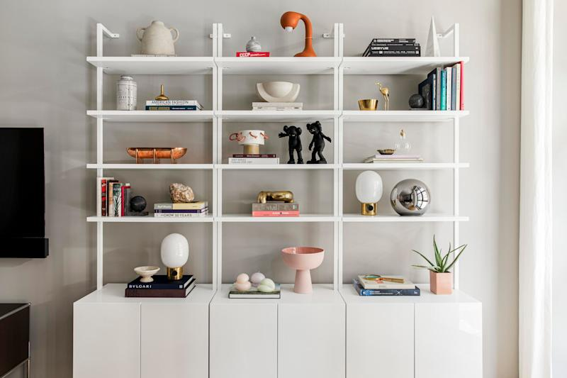 The three white Stairway bookshelves are stacked together and filled with accessories from CB2, Urban Outfitters, and Zara Home. Eye spy: a copper bowl by Brooklyn studio Fort Standard, JWDA table lamps by Danish studio Menu, and a burnt orange lamp by Entler.