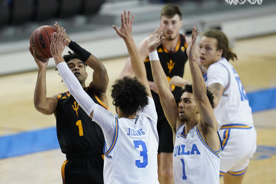 Arizona State guard Remy Martin (1) shoots against UCLA guards Johnny Juzang (3) and Jules Bernard (1) during the first half of an NCAA college basketball game Saturday, Feb. 20, 2021, in Los Angeles. (AP Photo/Ashley Landis)