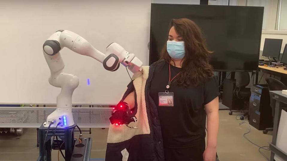 An MIT robot putting a jacket onto an engineer's arm inside of a lab.