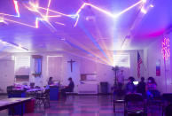 People sit and wait, Monday, May 17, 2021, at a COVID-19 vaccination clinic at St. Patrick Catholic Church in Canonsburg, Pa., which featured laser beams and music. George Dodworth, of Lightwave International, helped set up the vaccination site and decided to add lasers and music to try to make it more fun and ease some of the apprehension and anxiety younger groups might feel while getting the vaccine. (Emily Matthews/Pittsburgh Post-Gazette via AP)