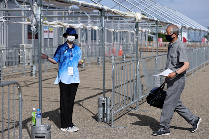 A masked man walks through a stadium ticket checkpoint with no line at the Olympics.