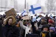 A group of people hold placards during a protest against the Finnish government's regulations to fight the coronavirus pandemic in Helsinki, Saturday, March 20, 2021. Some 400 protesters gathered peacefully in downtown Helsinki. (Antti Aimo-Koivisto/Lehtikuva via AP)