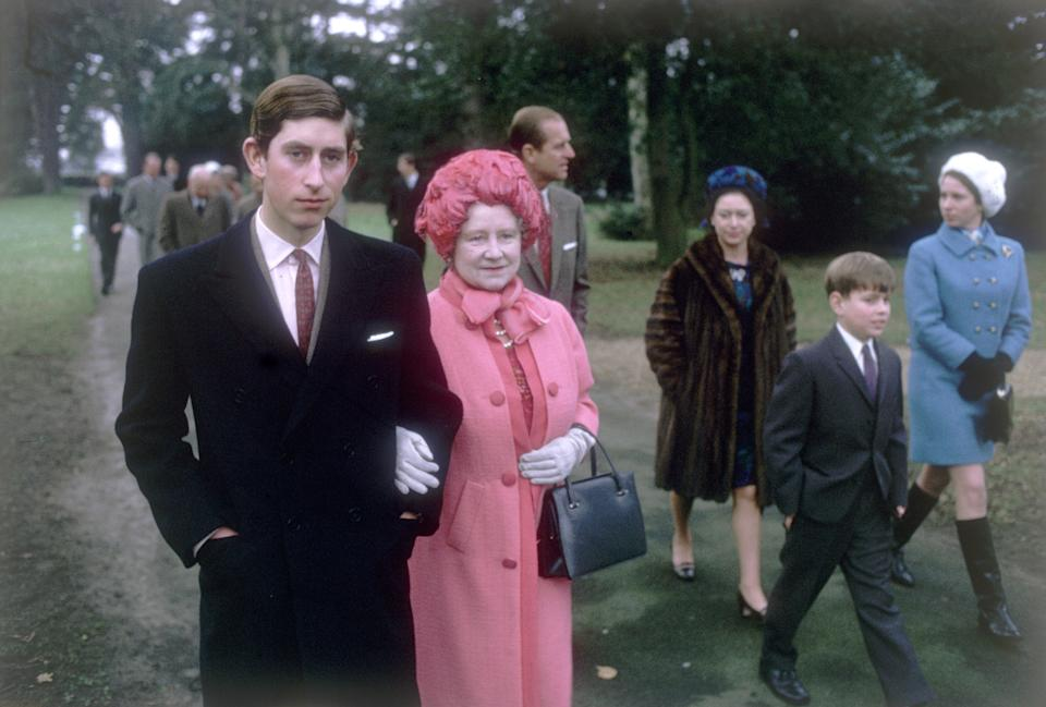 1969:  Prince Charles arm in arm with Queen Elizabeth the Queen Mother (1900 - 2002) at Sandringham. Prince Philip the Duke of Edinburgh, Princess Margaret, Princess Anne and Prince Andrew all walk behind them.  (Photo by Fox Photos/Getty Images)