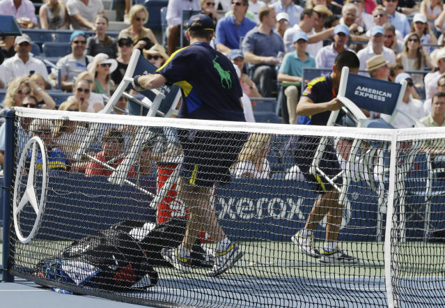Ball persons return chairs and tennis gear to the sidelines after a gust of wind blew them onto the court during a semifinal match between Britain's Andy Murray and Tomas Berdych, of the Czech Republic, at the 2012 US Open tennis tournament, Saturday, Sept. 8, 2012, in New York. (AP Photo/Darron Cummings)