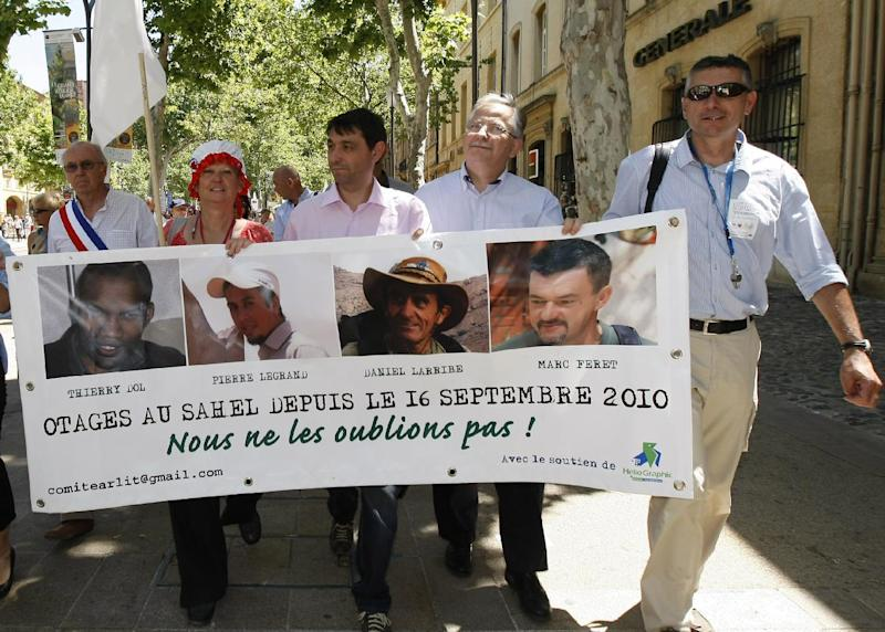 FILE - This Saturday, June 22, 2013, file photo shows hostage's families, friends and activists demonstrating, in Aix en Provence, southern France, to mark 1,000 days since four French hostages were kidnapped in Niger. President Francois Hollande says four Frenchmen taken hostage by Islamic extremists in Niger have been released, Tuesday, Oct, 29, 2013. The four were taken in September 2010 from their dormitories in the town of Arlit, where they worked for the French nuclear company Areva. The portraits show from left : Thierry Dol, Pierre Legrand, Daniel Larribe and Marc Feret. (AP Photo/Claude Paris, File)