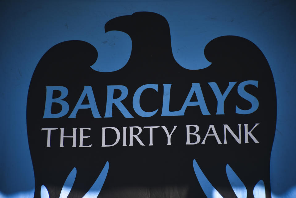 Greenpeace activists gather at the main entrance of Barclays bank hedquarters in Canary Wharf in protest over the bank's refusal to stop funding pipelines that take oil from Canada's tar sands to market in the USA and Asia, London on July 19, 2018. Activists scaled the entrance to redress the headquaters sign in an oil drip effect as well as others entering the building dressed as bankers whilst playing recorded messages from Barclays customers that are in opposition to the bank's funding of the tar sands pipelines. (Photo by Alberto Pezzali/NurPhoto via Getty Images)