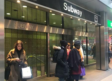 Passengers stand outside King subway station after a bomb threat was made in Toronto
