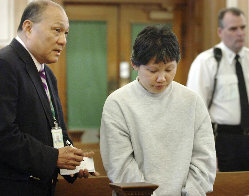 FILE - In this April 5, 2011 file photo, court interpreter Gar Chiang, left,  speaks to Li Rong Zhang, of Quincy, Mass., during her arraignment in Norfolk Superior Court in Dedham, Mass., on charges she murdered her 8-year-old son in January by lighting a hibachi grill in a bedroom of their apartment. The U.S. Justice Department says many state courts are violating people's constitutional rights by not providing language interpreters for no charge for all their programs. (AP Photo/Gary Higgins, Pool, File)
